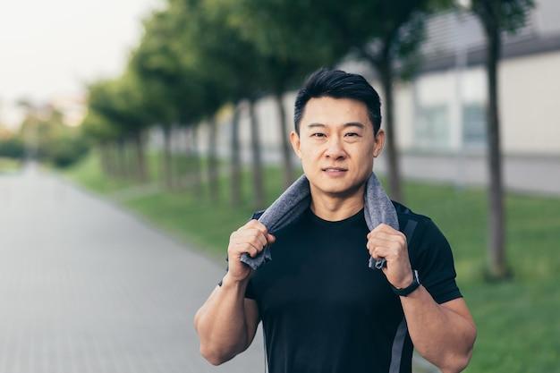 Aziatische man na fitnesstraining en joggen, een gelukkige man die lacht, laat zijn duim zien en kijkt naar de camera