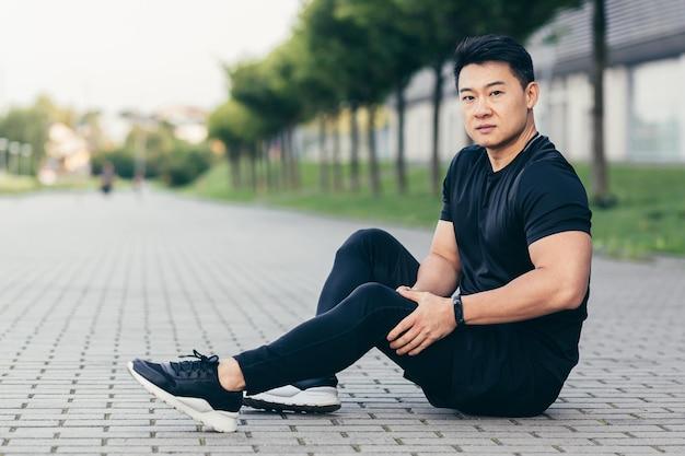 Aziatische man na fitnesstraining en joggen zit op de grond en lijdt aan pijn in de benen, masseert beenspieren