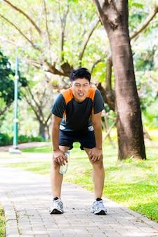 Aziatische man neemt ademloze pauze van hardlopen