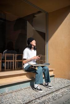 Aziatische man neemt een pauze van skateboarden