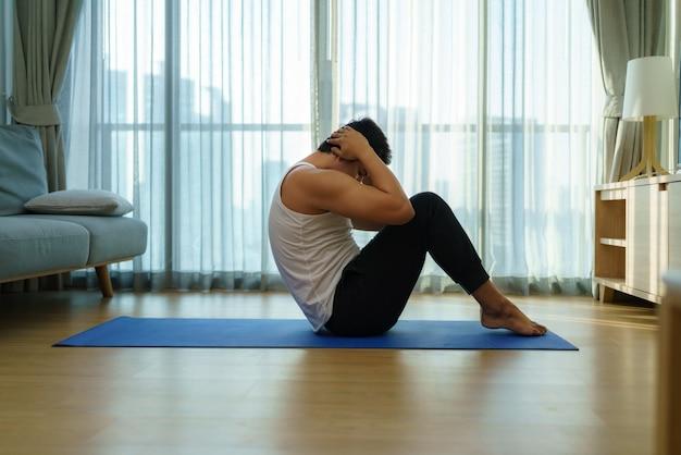 Aziatische man oefent thuis door rechtop te gaan zitten tijdens de sluiting van de sportschool tijdens de covid-19-uitbraak.