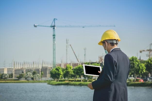 Aziatische man of zakenman enquête op de bouw van onroerend goed op de site