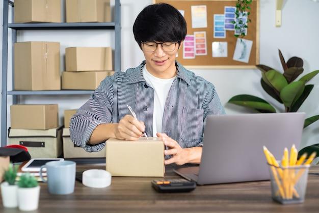Aziatische man ondernemer opstarten kleine onderneming ondernemer mkb freelance man aan het werk met doos aan online marketing verpakking en levering scène thuis kantoor, onlinebusiness verkoper concept.