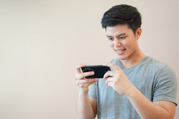 Aziatische man online gametoepassing spelen met gevoel opgewonden in ontspan tijd