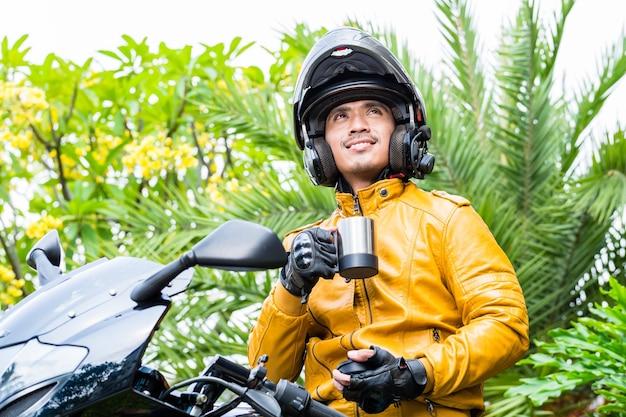 Aziatische man op motorfiets met helm met koffiepauze