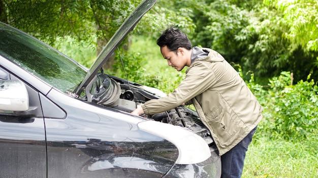 Aziatische man opende de motorkap en controleerde de auto