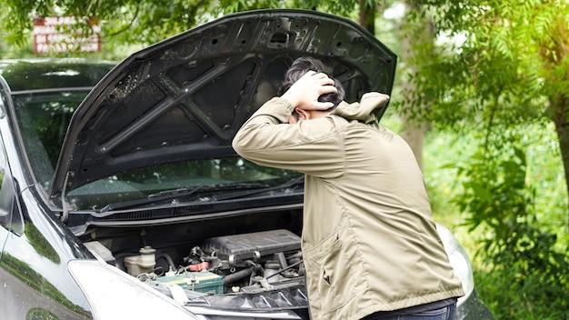Aziatische man opende de motorkap van de auto terwijl hij verward was