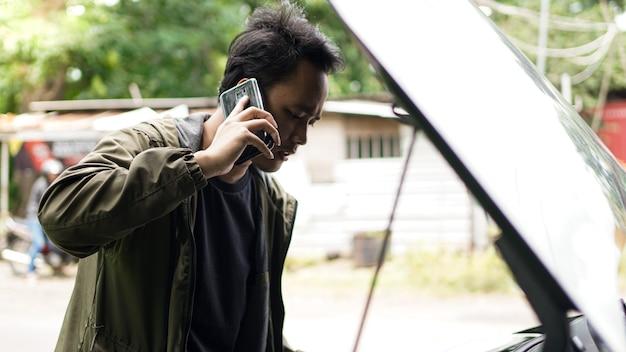 Aziatische man opende de motorkap van de auto tijdens het bellen