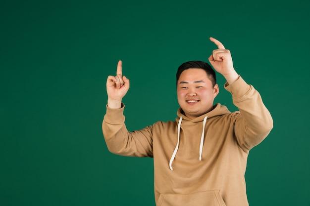 Aziatische man portret geïsoleerd over groene muur met copyspace
