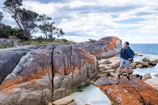Aziatische man poseert in de bay of fire in tasmanië, australië