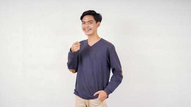 Aziatische man poseren naar voren wijzend met lachende uitdrukking geïsoleerd op een witte achtergrond