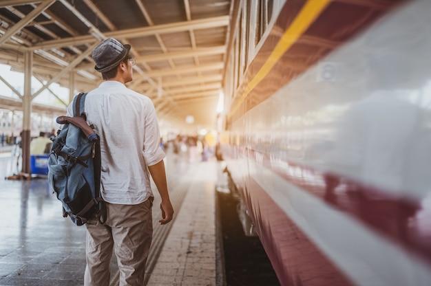 Aziatische man reiziger met rugzak in de spoorweg, rugzak en hoed op het treinstation met een reiziger. reisconcept. man reiziger toerist wandelen op treinstation.