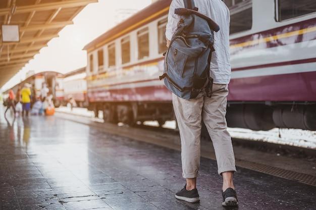Aziatische man reiziger met rugzak in de spoorweg, rugzak op het treinstation met een reiziger. reisconcept. man reiziger toerist wandelen op treinstation.