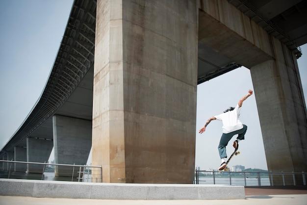 Aziatische man skateboarden in de stad buiten