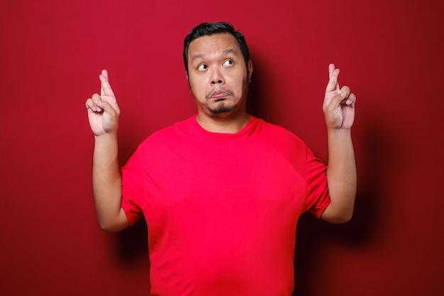 Aziatische man sluit zijn mond en kruist de vingers en maakt een beloftegebaar over rode achtergrond