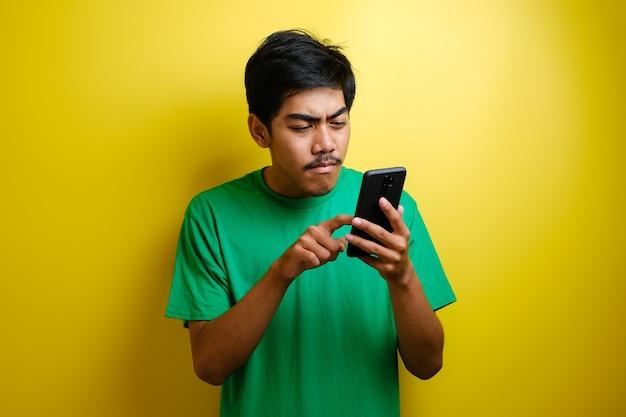 Aziatische man speelt mobiel spel op zijn smartphone met serieuze of boze uitdrukking tegen gele achtergrond