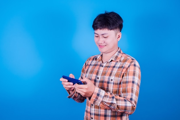 Aziatische man spelen op tablet slimme telefoon tegen op blauwe achtergrond