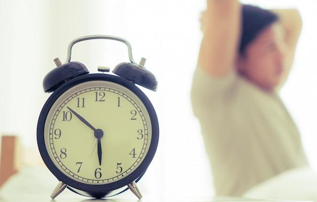 Aziatische man strekt zich uit na wakker met wekker zes uur weergegeven