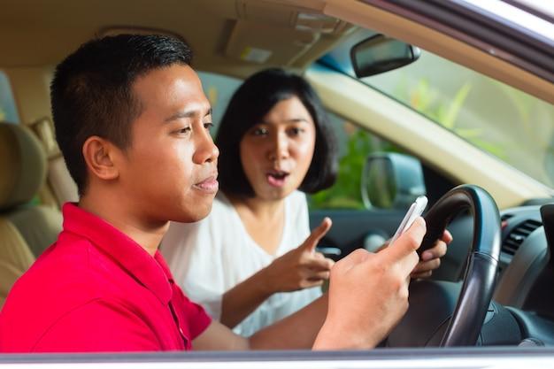 Aziatische man texting tijdens het rijden