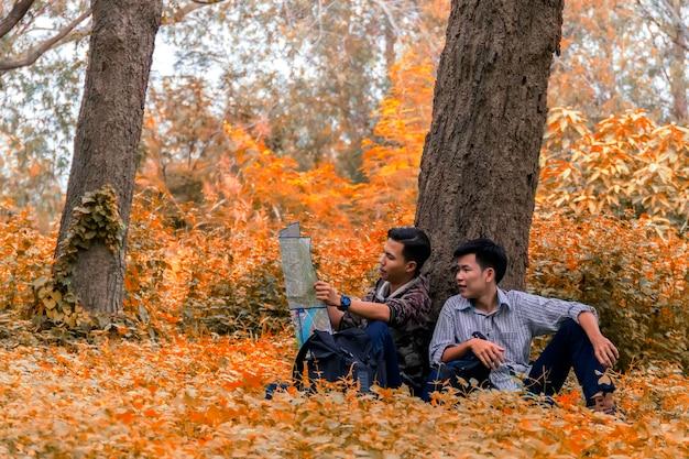 Aziatische man toeristen met rugzak naar het bosseizoen herfst kijkend naar kaart om wandelpaden te leren.