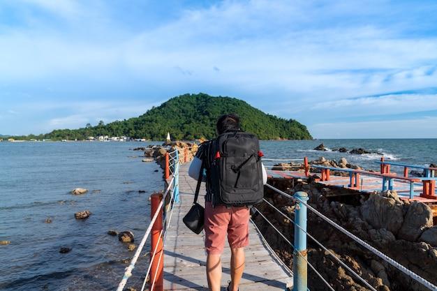 Aziatische man toeristische backpaker lopen op houten brug met touw spoorbrug gezichtspunt om pagode te zien