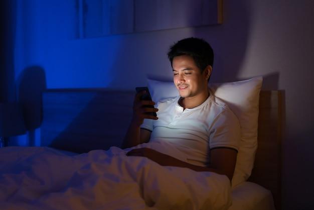 Aziatische man typt online chat met een vriend of vriendin 's nachts op een bed in een slaapkamer die uit het licht is.