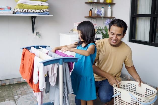 Aziatische man vader gezinshoofd en kind dochter in kleren drogen wasgoed