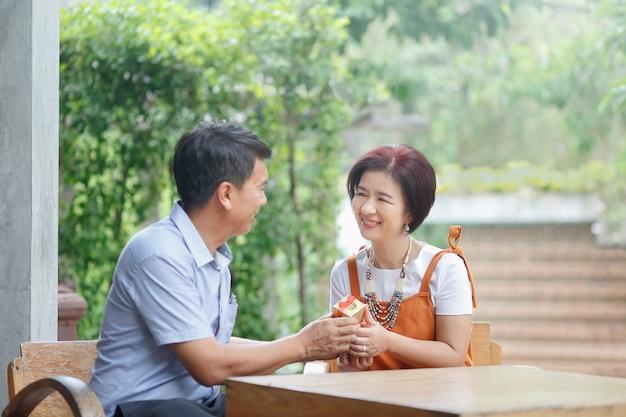 Aziatische man van middelbare leeftijd geeft een cadeau aan zijn vrouw op de huwelijksdag van de verjaardag