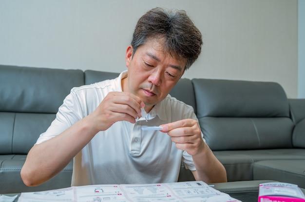 Aziatische man van middelbare leeftijd getest op coronavirus met behulp van covid-19 thuisantigeenkits.