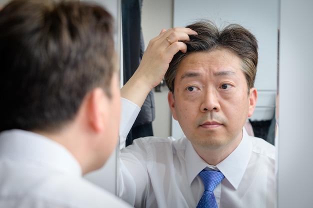 Aziatische man van middelbare leeftijd in de spiegel kijken en zijn haar aan te raken