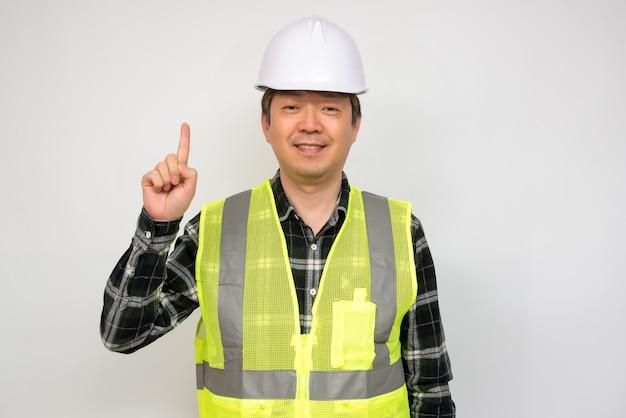 Aziatische man van middelbare leeftijd in een lichtgroen werkvest en witte veiligheidshoed.