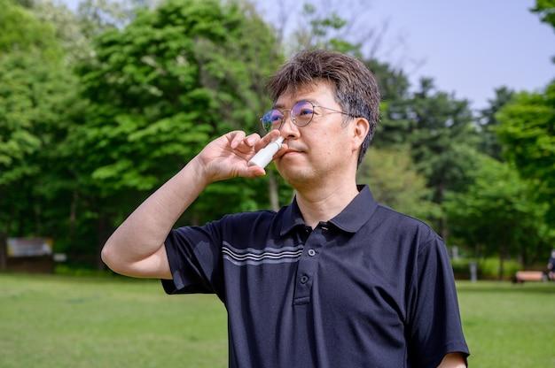 Aziatische man van middelbare leeftijd met neusspray buitenshuis.