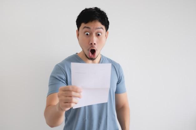 Aziatische man verrast en geschokt door de brief in zijn hand op geïsoleerde muur.