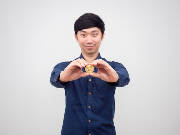 Aziatische man vrolijk toont hand met gouden bitcoin op witte achtergrond
