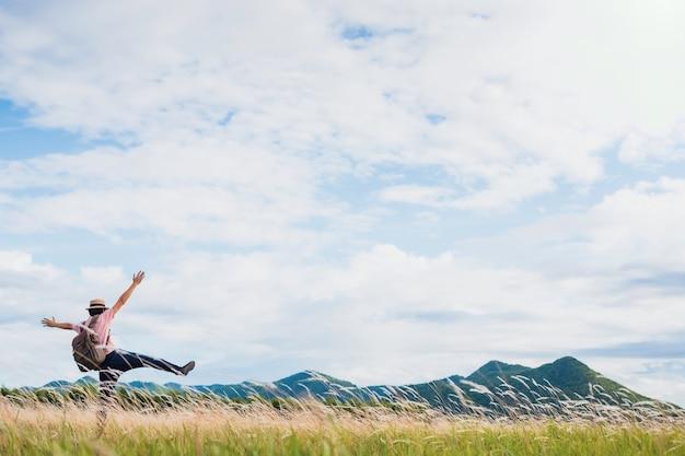 Aziatische man wandelen en foto nemen in weide bloem veld landschap achtergrond. concept van reizen in het zomerseizoen in thailand.