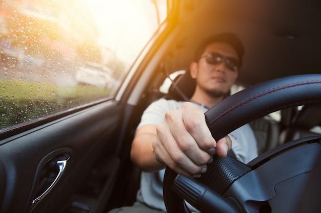 Aziatische man ware zon glas rijden een auto