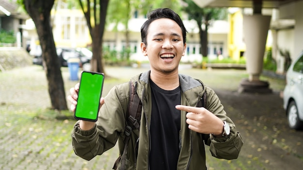 Aziatische man wees met een glimlach op de mobiele telefoon met groen scherm