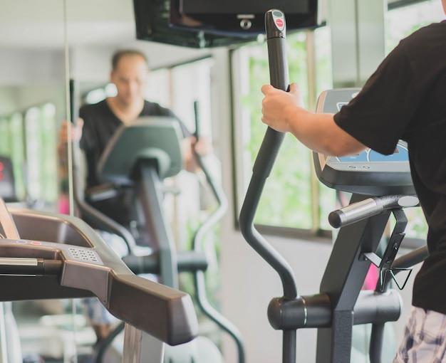 Aziatische man werken oefening bij gym gewichtsverlies