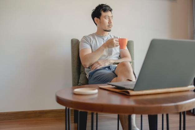 Aziatische man werkt met zijn laptop en koffie drinken.