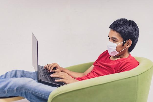 Aziatische man werkt vanuit huis tijdens coronavirus of covid-19. draag een gezichtsmasker ter bescherming tegen coronavirus, werk thuis en gebruik een laptop. werk vanuit huis, blijf thuis. sociale afstand.