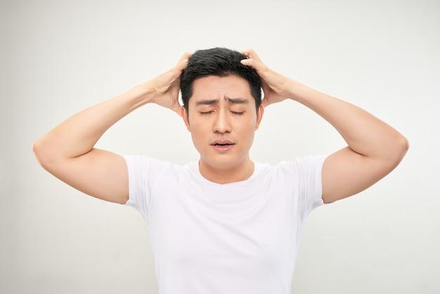Aziatische man wit overhemd voelt hoofdpijn en raakt het hoofd aan met twee handen op een witte achtergrond