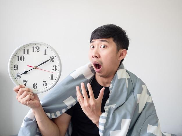 Aziatische man wordt wakker met een deken omhulsel en voelt zich verveeld bij het kijken naar de klok in de hand