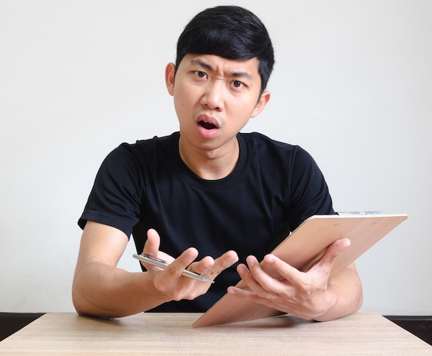 Aziatische man zit aan het bureau met pen en klembord in de handregistreer baanconcept