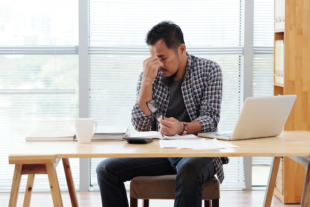 Aziatische man zit aan tafel met laptop en documenten en wrijven voorhoofd benadrukt