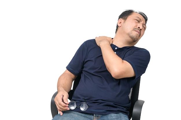 Aziatische man zit op een stoel en lijdt aan nek- of schouderpijn op wit wordt geïsoleerd
