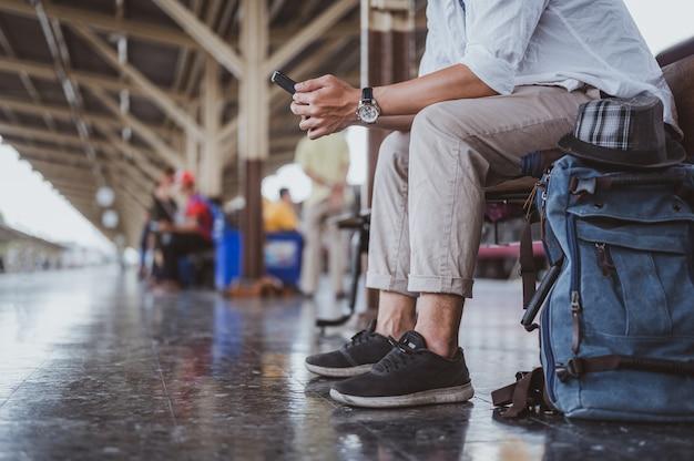 Aziatische man zoekt de juiste richting op treinstation.reiziger wachtende trein en vakantievakantie plannen met smartphone. vakantie, reis, reis en zomer travel concept.