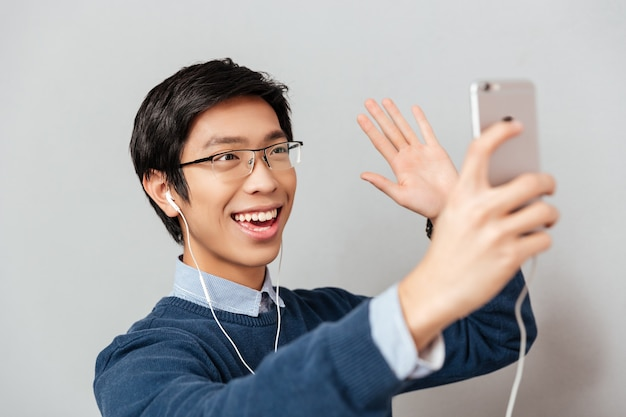 Aziatische man zwaaien in de telefoon. model met bril