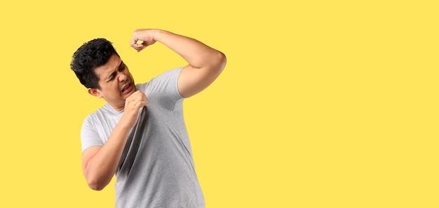 Aziatische man zweten overmatig ruiken slecht geïsoleerd op geel