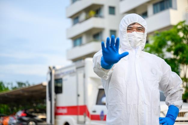 Aziatische mannelijke arts blijf bij een ambulance voor noodgevallen met een pbm-pak en een masker. ziekenhuisuitgang, poliklinische quarantainetent, intensive care-centrum in covid19-ziekenhuis