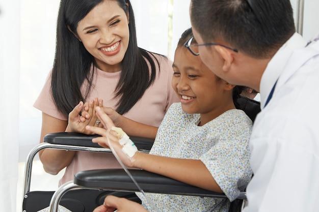 Aziatische mannelijke arts die aan jonge kindrolstoel en moeder, de zorg van het conceptaziathuis spreekt